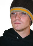Serious Young Man. Isolated picture of a serious young man wearing a sweatshirt and beanie hat stock photo