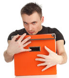 Serious young man with big orange box Royalty Free Stock Images