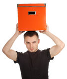 Serious young man with big orange box Stock Images