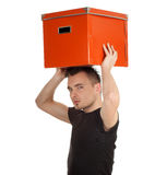 Serious young man with big orange box Stock Photography