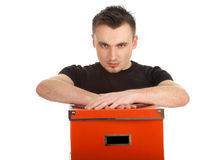 Serious young man with big orange box Royalty Free Stock Image