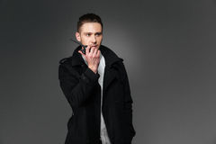 Serious young man in black coat talking in walkie talkie Stock Photo