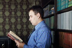 Serious young man in blue reads book Royalty Free Stock Photography