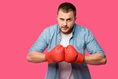 serious young man in boxing gloves looking at camera isolated