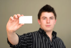 Serious Young Man with Business Card. Casual young man with serious face holding out blank business card. Shallow DOF stock images