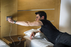 Serious Young Man Connecting a Phone to a Charger. Serious Gorgeous Young Man Connect his Mobile Phone to a Charger While Lying on his Side on the Bed Royalty Free Stock Image
