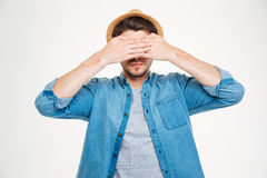 Serious young man covered his eyes by hands Royalty Free Stock Image