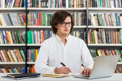 Serious young man with dark hair  sitting at a desk in the libra Royalty Free Stock Photos