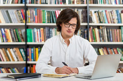 Serious young man with dark hair sitting at a desk in the librar Royalty Free Stock Image