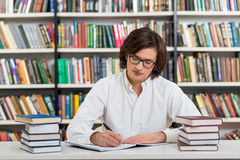 Serious young man with dark hair sitting at a desk in the librar Stock Photography