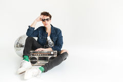 Serious young man with disco ball and boombox. Picture of serious young man wearing sunglasses sitting  over white background with disco ball and boombox Stock Photo
