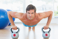 Serious young man doing push ups in gym Royalty Free Stock Photo