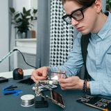 Serious young man fixing mobile phone free space. Attentive geek in glasses examing broken smartphone, repair shop workplace with tools. Electronic fixing royalty free stock photo