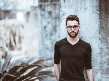 Serious young man in glasses, portrait. Portrait of serious handsome bearded hipster guy in the glasses and black t-shirt standing in front of the concrete wall Royalty Free Stock Image
