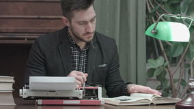 Serious young man with glasses sitting at the desk with typewriter and reading book stock footage