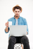 Serious young man in hat drinking coffee and using laptop Stock Image