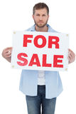 Serious young man holding a for sale sign. Serious young man on white background holding a for sale sign Stock Image