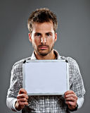 Serious young man holding sign Stock Image