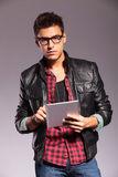 Serious young man holding a tablet pad Stock Photo
