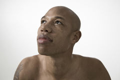 Serious Young Man Looking Up. Closeup of an African American man looking up against gray background Royalty Free Stock Image