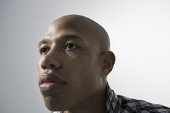 Serious Young Man Looking Up. Closeup of an African American man looking up against gray background Stock Image