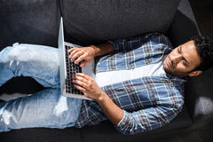 Serious young man lying on sofa and using laptop, small business people concept. High angle view of serious young man lying on sofa and using laptop, small Royalty Free Stock Images