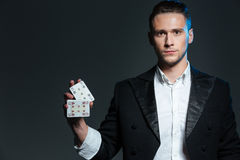 Serious young man magician standing and holding two playing cards Stock Photos