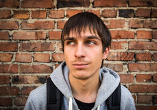 Serious Young Man outdoor. Sad Young Man on the Brick Wall Background stock images