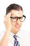 Serious young man with plaster on his forehead having a headache Stock Images