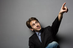 Young man pointing upwards. Serious young man pointing upwards on plain gray background Stock Images