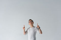 Serious young man points his forefingers up. Handsome young caucasian man pointing up with index fingers upwards, looking up, standing against gray background in Stock Photography