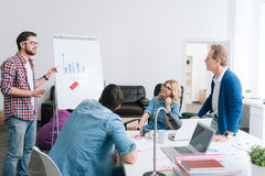 Serious young man presenting a diagram. Statistical data. Serious young handsome men standing hear the whiteboard and presenting a diagram while presenting a royalty free stock photos