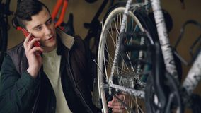 Serious young man bike repairman is checking and turning wheel while talking on mobile phone. Bicycle maintenance. Serious young man professional bike repairman stock footage