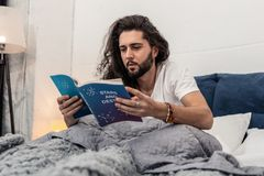 Serious young man reading about stars and destiny. Studying astrology. Serious young man reading a book about stars and destiny while sitting at home royalty free stock photo