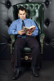 Serious young man reads book in leather armchair Royalty Free Stock Photography