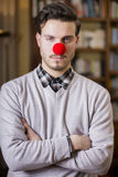 Serious young man with red clown nose Royalty Free Stock Image