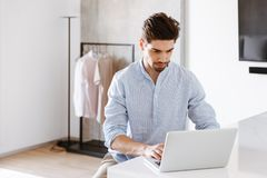Serious young man in shirt using laptop computer. While sitting at home Stock Photo