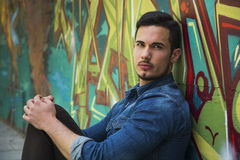 Serious young man sitting against colorful graffiti wall Stock Images