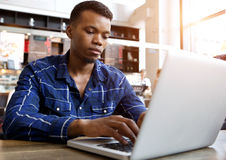 Serious young man sitting in cafe using laptop Stock Photos