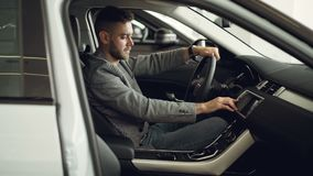 Serious young man is sitting inside new car in motor showroom and checking electronics pressing buttons on control panel