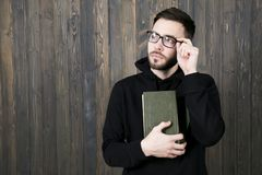 serious young man with a small beard in glasses and in black clothes with books in his hand squinting looking up, holding his royalty free stock photos