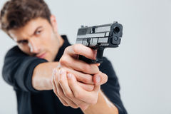 Serious young man standing and aiming with gun Royalty Free Stock Photos