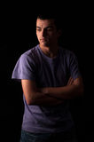 Serious young man standing with arms crossed on black background Royalty Free Stock Images