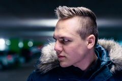 Serious young man staring intently to the side. Serious young man with a modern haircut standing outdoors in town staring intently to the side in a fur trimmed Stock Photos