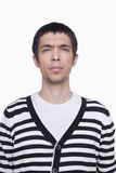 Serious Young man in striped shirt looking at camera, studio shot Stock Photos