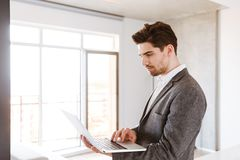 Serious young man in suit using laptop computer. While standing at home Stock Image
