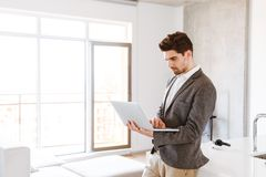 Serious young man in suit using laptop computer. While standing at home Royalty Free Stock Photo