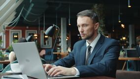 Serious young man in suit using laptop typing working alone in restaurant