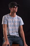 Serious young man with sunglasses and baseball hat, si Royalty Free Stock Image