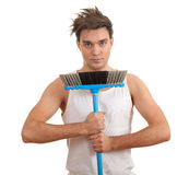 Serious young man with sweeping brush Royalty Free Stock Image
